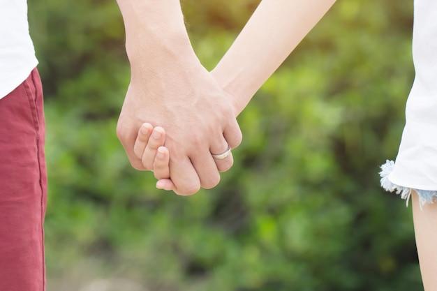 Mano maschio che tiene bella mano femminile con anello