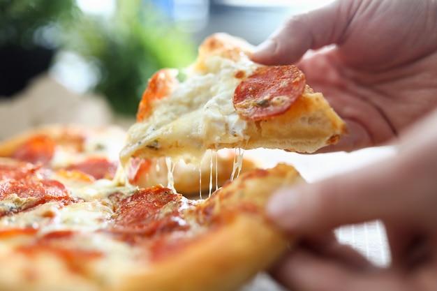 Mano maschio che tiene grande pezzo di gustosa pizza fresca