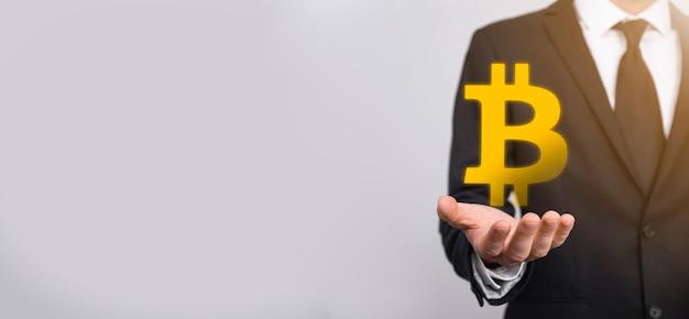 Mano maschio che tiene un'icona bitcoin su sfondo blu. bitcoin cryptocurrency bit digitale coin btc valuta tecnologia business internet concept.