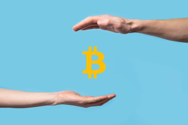 Mano maschio che tiene un'icona di bitcoin sulla superficie blu