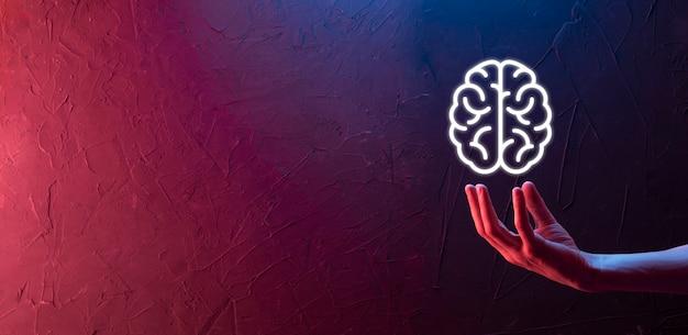 Mano maschio che tiene l'icona del cervello su sfondo rosso e blu al neon. intelligenza artificiale machine learning business internet technology concept.banner con spazio di copia
