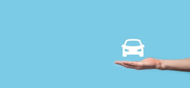 Mano maschio che tiene icona auto auto sulla superficie blu