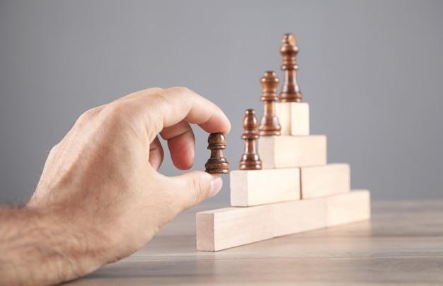 Mano maschio che tiene pezzo degli scacchi su blocchi di legno.