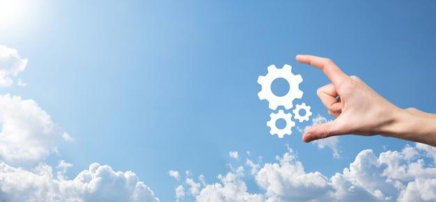 Mano maschile che tiene l'icona degli ingranaggi dentati, icona del meccanismo su schermi virtuali su sfondo blu. concetto di affari del sistema di processo di tecnologia del software di automazione. banner