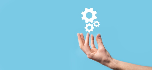 Mano maschio che tiene l'icona degli ingranaggi del dente, icona del meccanismo sugli schermi virtuali su priorità bassa blu. concetto di affari del sistema di processo della tecnologia del software di automazione. banner.