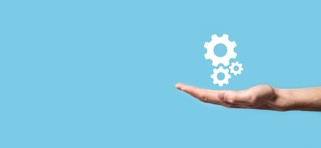 Mano maschio che tiene l'icona degli ingranaggi del dente, icona del meccanismo sugli schermi virtuali su priorità bassa blu. concetto di affari del sistema di processo della tecnologia del software di automazione.