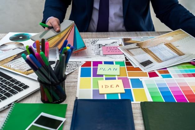 Campioni di colore della tenuta della mano maschio con prospettiva interna. la mano dell'interior designer che lavora con schizzi di appartamenti, campioni di materiali e colori