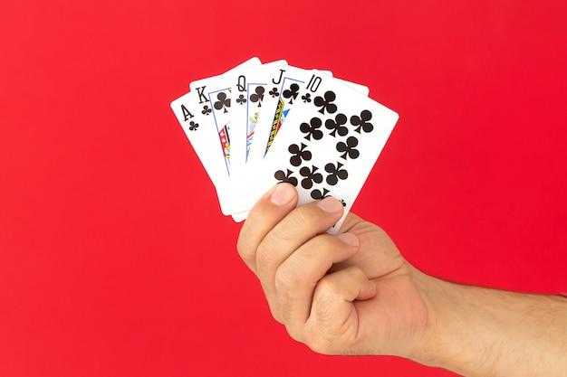Mano maschio che tiene la combinazione di carte da poker scala reale su sfondo rosso. casinò fortuna fortuna concetto