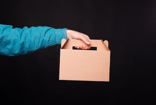 Mano maschio che tiene la scatola di cibo per la consegna su sfondo scuro