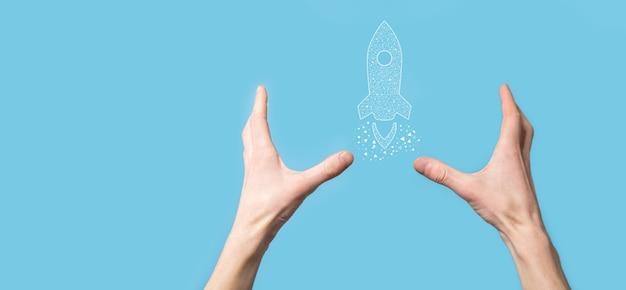 Mano maschio che tiene icona razzo digitale trasparente. il razzo sta lanciando e vola in volo. concetto di idea imprenditoriale.
