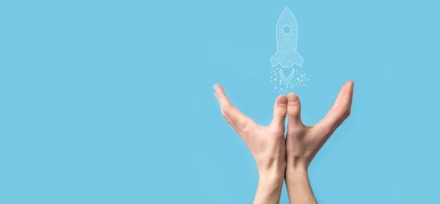 Mano maschio che tiene icona razzo digitale trasparente. concetto di affari di avvio. il razzo sta lanciando e vola in volo. concetto di idea imprenditoriale.