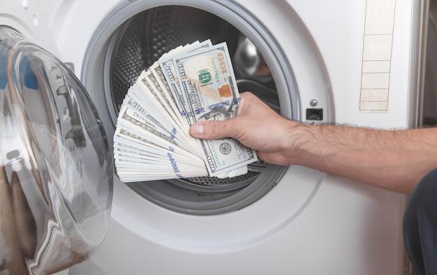 Mano maschio che tiene dollaro in lavatrice riciclaggio di denaro