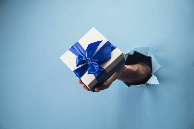 Mano maschio che tiene un regalo su una scena blu