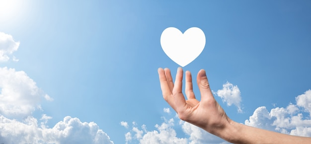 Cuore maschio della tenuta della mano, come icona su fondo blu. gentilezza, carità, puro amore e concetto di compassione. banner con spazio di copia.