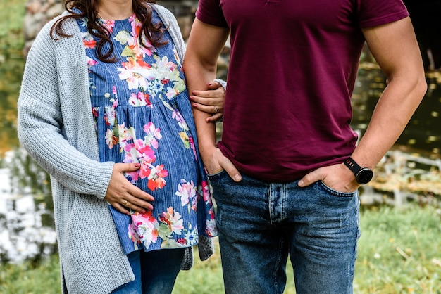 Mano maschio che tiene la mano della moglie incinta. donna incinta che abbraccia la pancia.