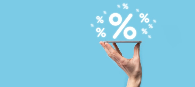 Mano maschio che tiene l'icona percentuale del tasso di interesse su sfondo blu. tasso di interesse finanziario e concetto di tassi ipotecari. banner con spazio di copia