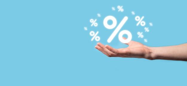 Mano maschio che tiene l'icona percentuale del tasso di interesse su sfondo blu. concetto di tassi finanziari e ipotecari di tasso di interesse. banner con spazio di copia