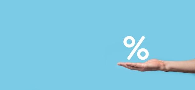 Icona di percentuale del tasso di interesse della holding della mano maschio su priorità bassa blu. concetto di tassi di interesse finanziario e ipotecario. banner con spazio di copia.