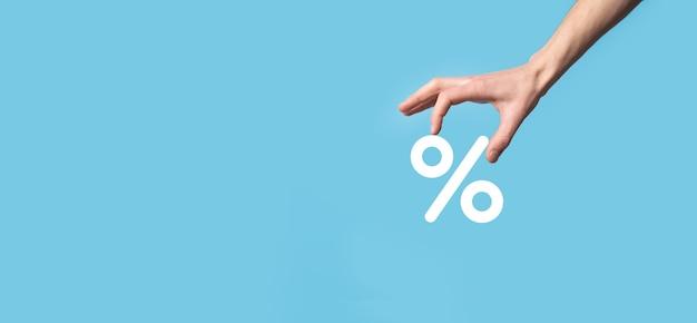 Icona di percentuale del tasso di interesse della holding della mano maschio su priorità bassa blu.