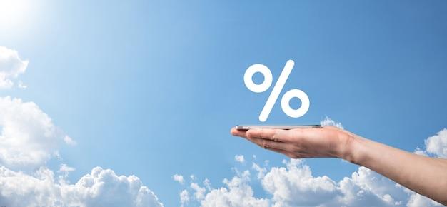 Icona di percentuale del tasso di interesse della holding della mano maschio sulla superficie del cielo blu