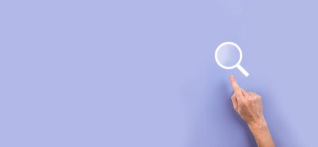 Mano maschio che tiene la lente d'ingrandimento, icona di ricerca su sfondo blu. concetto di ottimizzazione dei motori di ricerca, assistenza clienti. navigazione di informazioni sui dati in internet. concetto di rete.