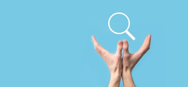 Mano maschio che tiene la lente di ingrandimento, icona di ricerca su sfondo blu. concetto di ottimizzazione dei motori di ricerca, assistenza clienti. navigazione di informazioni sui dati di internet. concetto di rete.