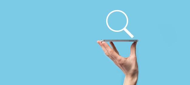 Mano maschio che tiene la lente d'ingrandimento, icona di ricerca su sfondo blu. concetto di ottimizzazione dei motori di ricerca, assistenza clienti. navigazione dati internet information. concetto di rete.