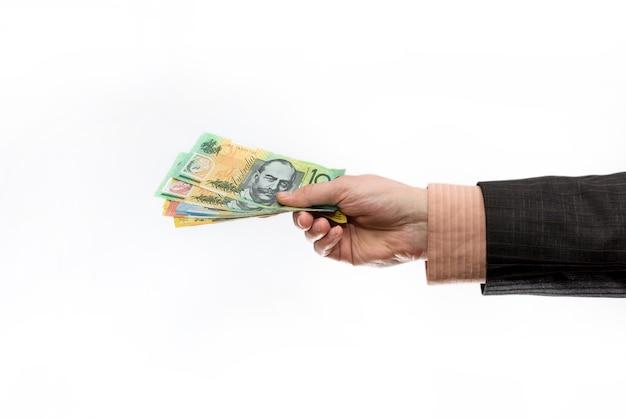 Mano maschio che tiene e che offre banconote in dollari australiani