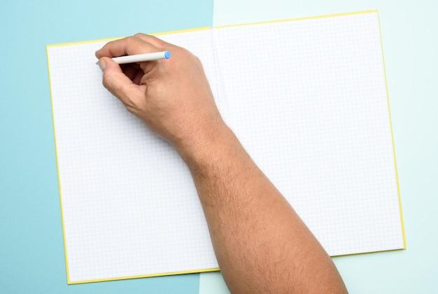 Mano maschio che tiene il blocco note aperto con fogli bianchi vuoti su un blu