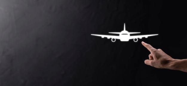 Mano maschio che tiene l'icona dell'aeroplano aereo su sfondo blu. acquisto di biglietti banner.nline. icone di viaggio sulla pianificazione del viaggio, trasporto, hotel, volo e passaporto. concetto di prenotazione del biglietto aereo.