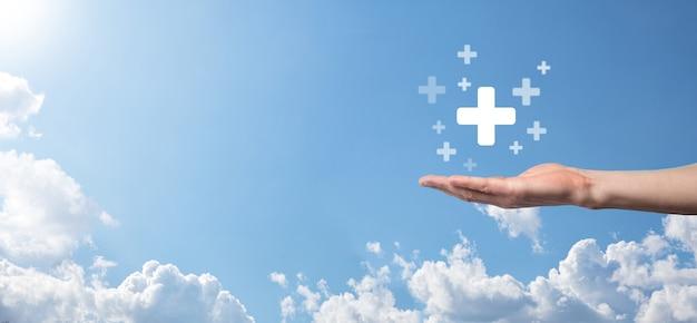 Mano maschio che tiene più icona su sfondo blu. segno più significa virtuale per offrire cose positive come benefici, sviluppo personale, social network profit, assicurazione sanitaria, concetti di crescita.