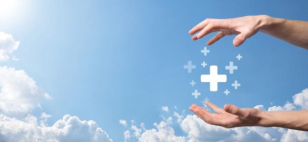 Mano maschio che tiene più icona su sfondo blu. segno più significa virtuale per offrire cose positive come benefici, sviluppo personale, social network profit, assicurazione sanitaria, concetti di crescita