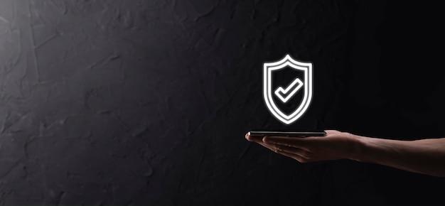 Mano maschio che tiene lo scudo protettivo con un'icona del segno di spunta su sfondo blu. protezione del computer di sicurezza della rete e sicurezza del concetto di dati.