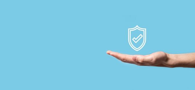 Mano maschio che tiene protegge lo scudo con un'icona di segno di spunta su sfondo blu. protezione del computer di sicurezza della rete e protezione del concetto di dati.