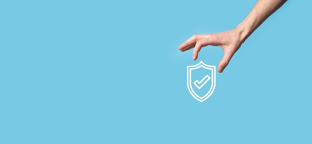 Mano maschio che tiene protegge lo scudo con un'icona di segno di spunta su sfondo blu.