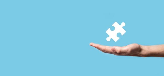 Icona di puzzle della holding della mano maschio su priorità bassa blu. pezzi che rappresentano la fusione di due società o joint venture, partnership, fusioni e concetto di acquisizione.