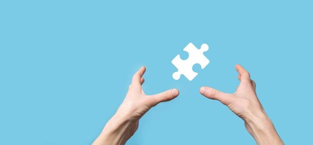 Icona di puzzle della holding della mano maschio sulla superficie blu