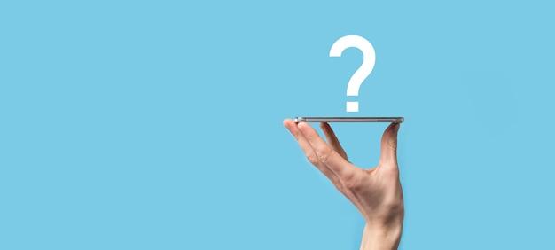 Icona del punto interrogativo della holding della mano maschio su priorità bassa blu. banner con lo spazio della copia. posto per il testo.