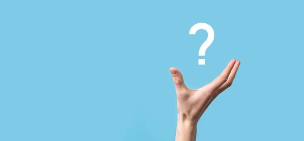 Icona del punto interrogativo della holding della mano maschio sulla superficie blu
