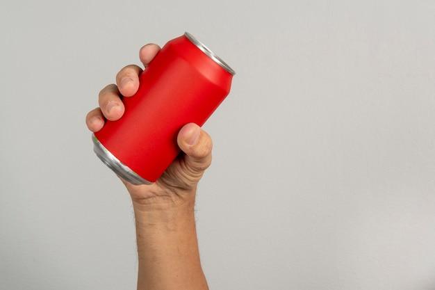 Mano maschile che tiene una lattina rossa in un muro grigio