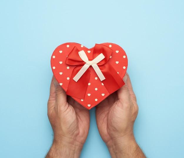 Mano maschio che tiene una scatola di cartone rossa con un fiocco su uno spazio blu, concetto di dare un regalo per una vacanza