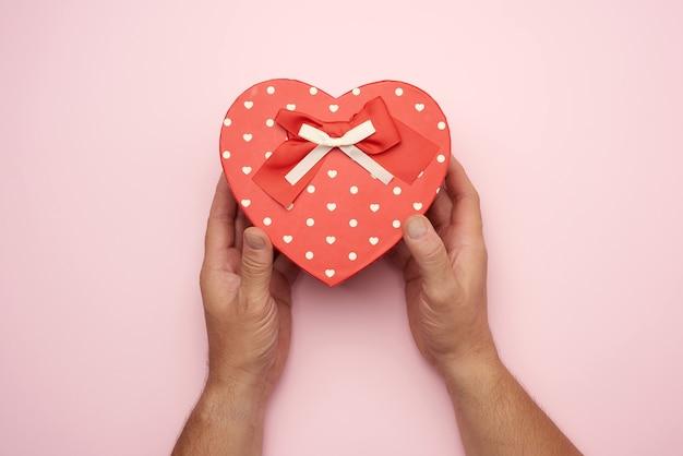 Mano maschio che tiene una scatola di cartone rossa con un fiocco, concetto di dare un regalo per una vacanza