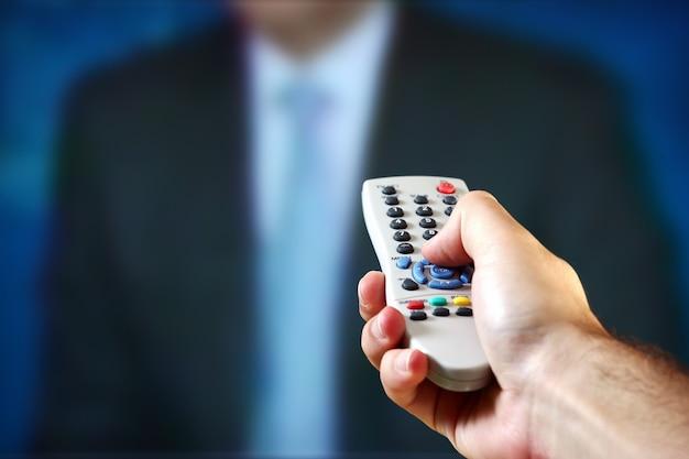 Una mano maschile che tiene un telecomando su un telegiornale