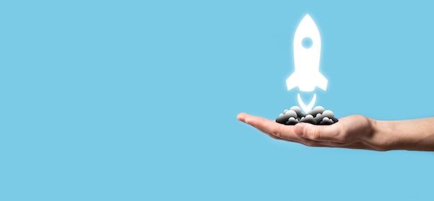 Mano maschile che tiene l'icona del razzo che decolla, lancia su sfondo blu. razzo sta lanciando e volando fuori, business start up, icon marketing su moderna interfaccia virtuale.start up concept.
