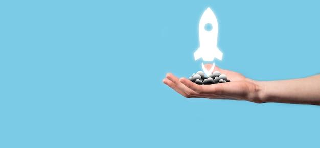 Mano maschile che tiene l'icona del razzo che decolla, lancia su sfondo blu. razzo sta lanciando e volando fuori, business start up, icon marketing su moderna interfaccia virtuale. concetto di avvio.
