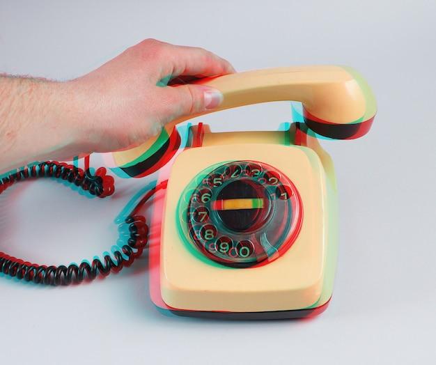Mano maschio che tiene una cornetta del telefono retrò rotante su un grigio