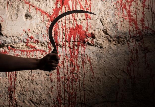 Mano maschile che tiene una falce davanti al muro macchiato di sangue in un concetto horror di halloween