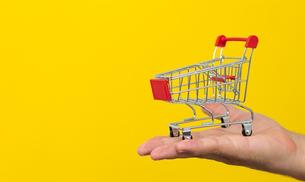 Mano maschio che tiene piccolo carrello del carrello su giallo. shopping online e concetto di consegna veloce