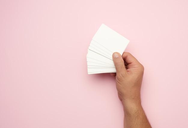 Mano maschio che tiene una pila di biglietti da visita bianchi in bianco, spazio della copia