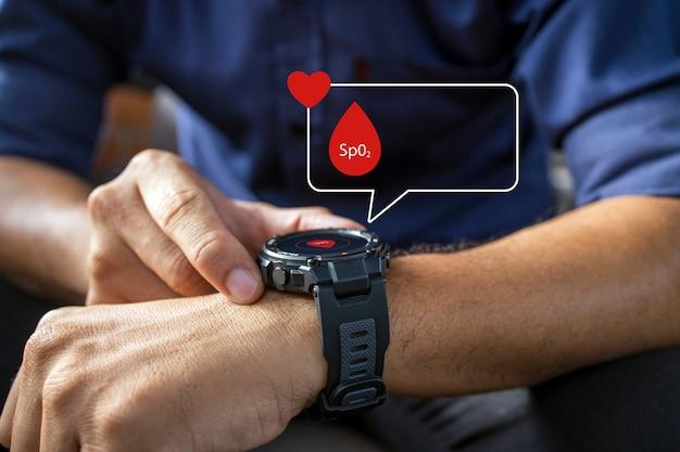 Mano maschile che tiene in mano un orologio intelligente con misurazione della frequenza cardiaca e dei livelli di ossigeno oxygen